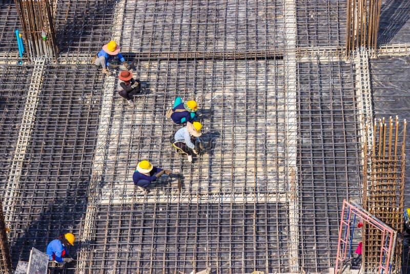 Trabajadores de construcción que fabrican la barra grande del refuerzo de la barra de acero en solar del área de la construcción imagenes de archivo