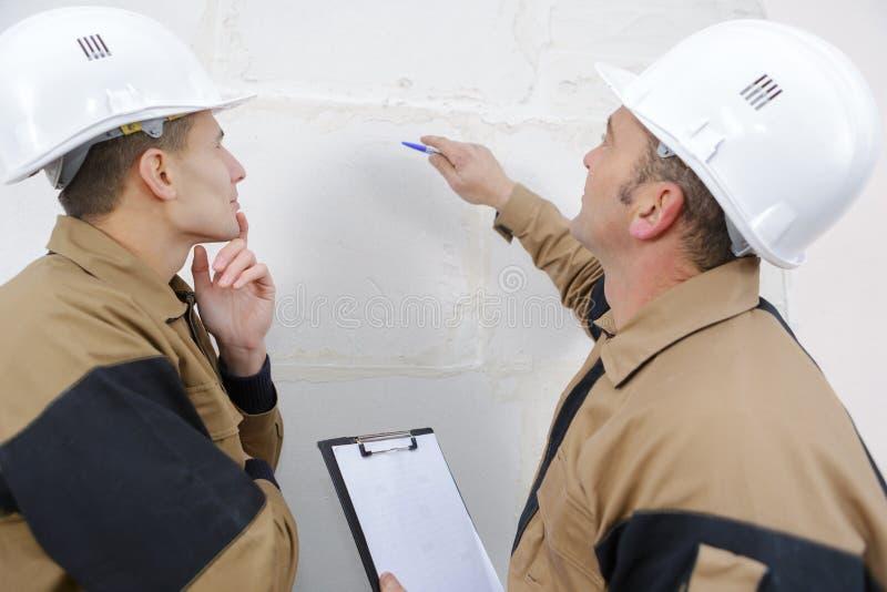 Trabajadores de construcción que hablan de la pared imagen de archivo