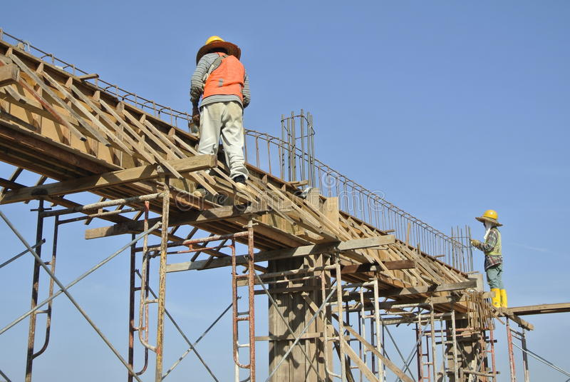 Trabajadores de construcción que instalan encofrado del haz y la barra del refuerzo foto de archivo libre de regalías