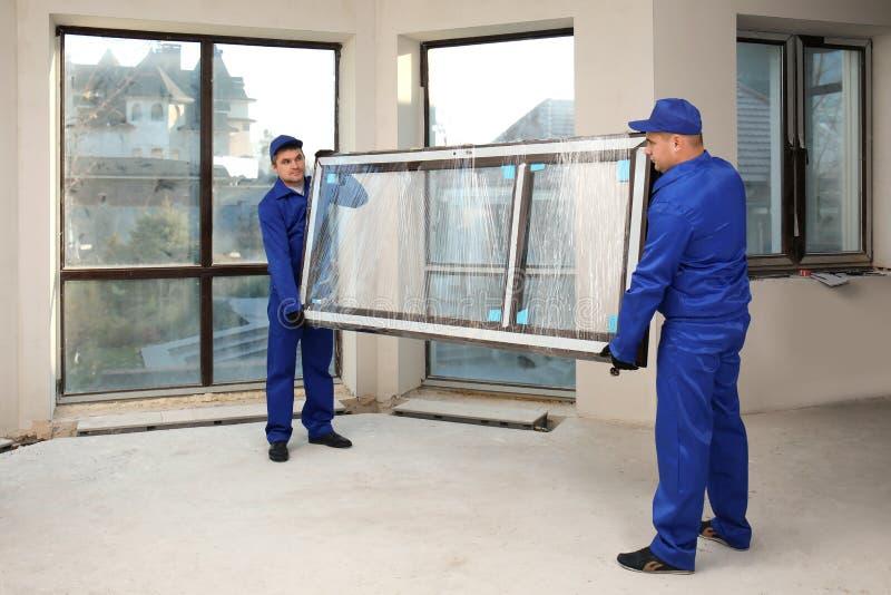 Trabajadores de construcción que llevan el vidrio de la ventana imágenes de archivo libres de regalías