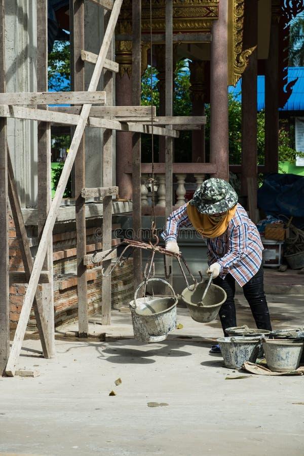 Trabajadores de construcción que mezclan el mortero fotos de archivo