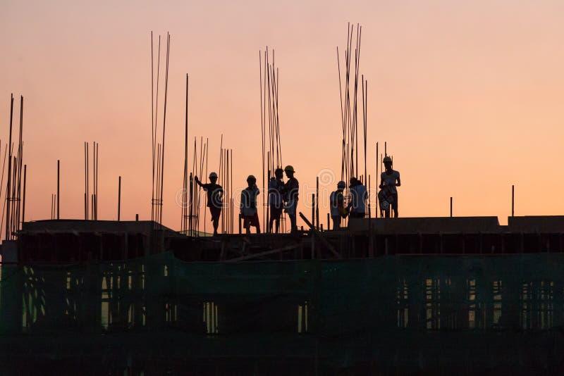 Trabajadores de construcción que trabajan en horas extras imágenes de archivo libres de regalías