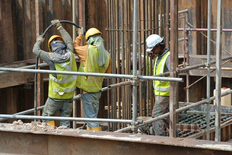 Trabajadores de construcción que usan el vibrador concreto para condensar el hormigón imagenes de archivo