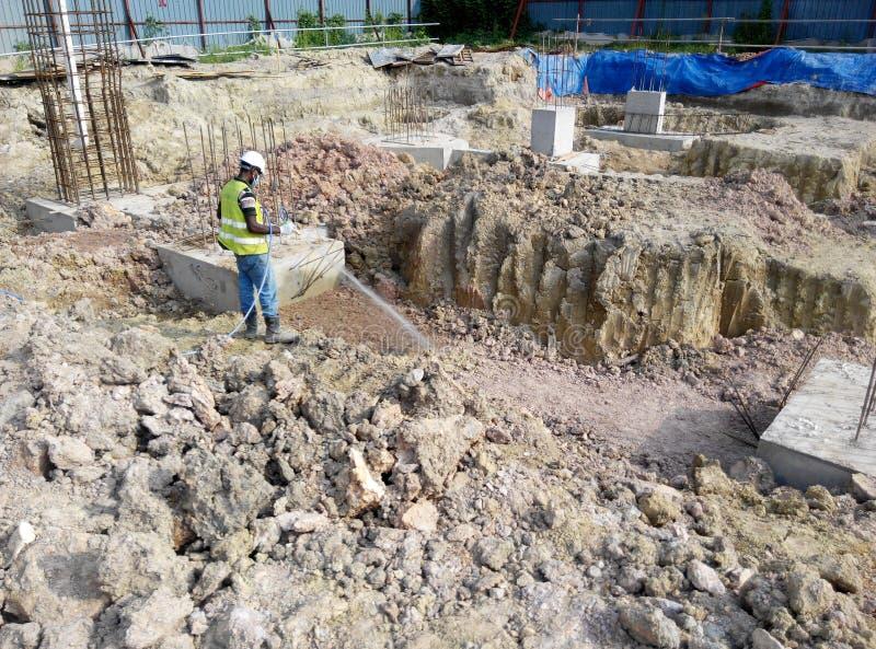 Trabajadores de construcción sraying el tratamiento químico de la termita anti al casquillo de pila fotos de archivo libres de regalías