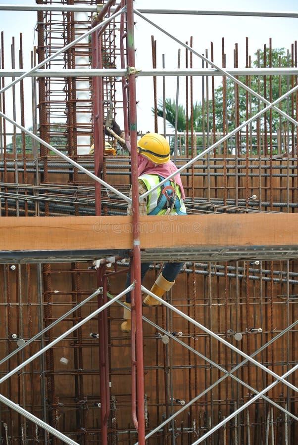 Trabajadores de construcci?n que fabrican la barra de acero del refuerzo dentro del encofrado de la madera en el emplazamiento de foto de archivo libre de regalías