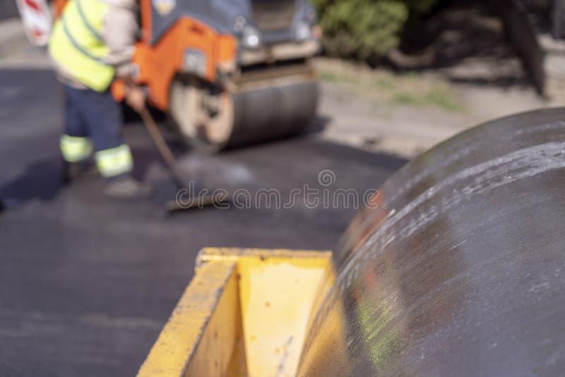 Trabajadores de la apisonadora de vapor y de construcción de carreteras en el sitio de la construcción de carreteras foto de archivo