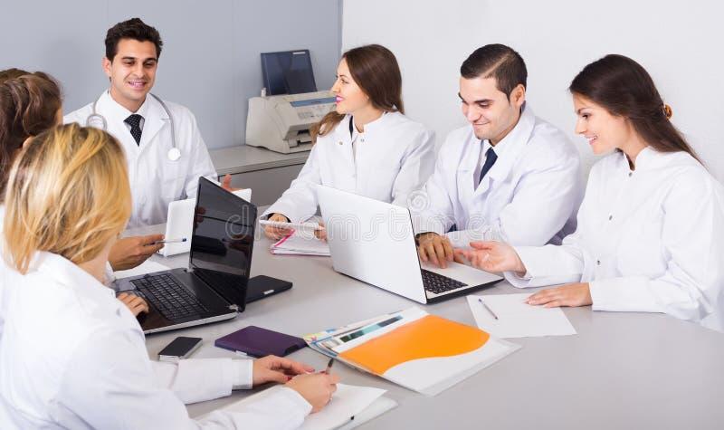 Trabajadores de la atención sanitaria y médico principal en el coloquio en clínica fotos de archivo libres de regalías