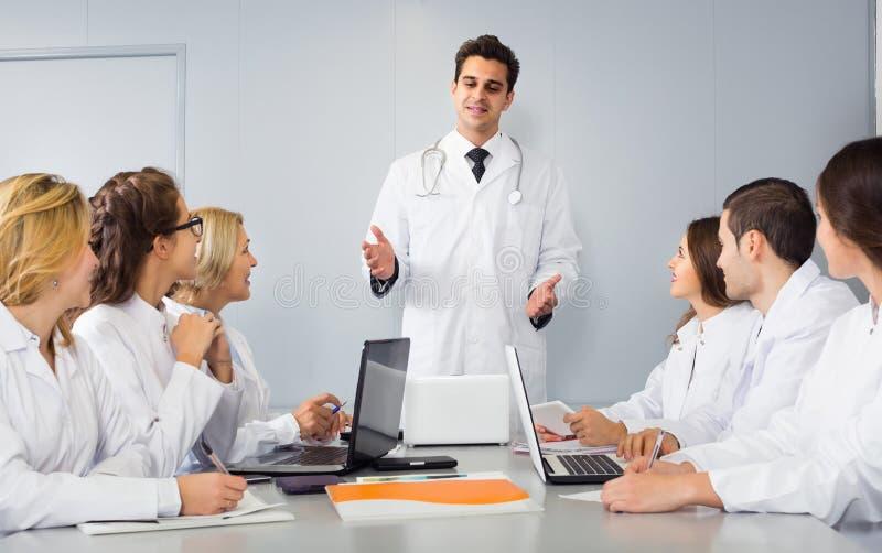 Trabajadores de la atención sanitaria y médico principal en el coloquio en clínica imagen de archivo