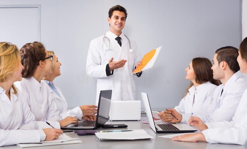 Trabajadores de la atención sanitaria y médico principal en el coloquio en clínica fotografía de archivo libre de regalías