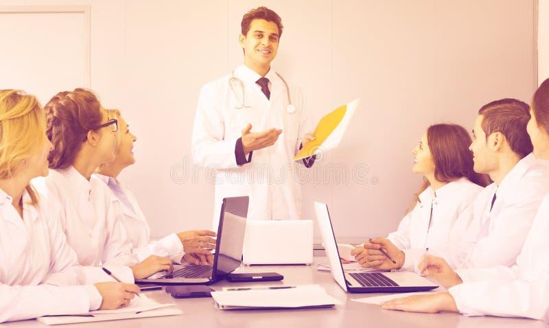 Trabajadores de la atención sanitaria y médico principal en el coloquio en clínica fotografía de archivo