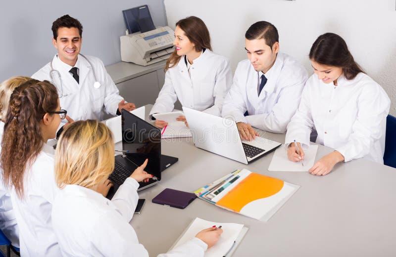 Trabajadores de la atención sanitaria y médico principal en el coloquio en clínica imágenes de archivo libres de regalías