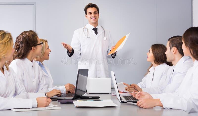 Trabajadores de la atención sanitaria y médico principal en el coloquio en clínica imagen de archivo libre de regalías