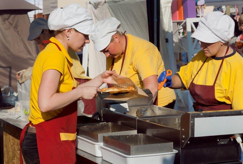 Trabajadores de la cocina de la comida rápida que cocinan platos en el friture para los clientes hambrientos imágenes de archivo libres de regalías