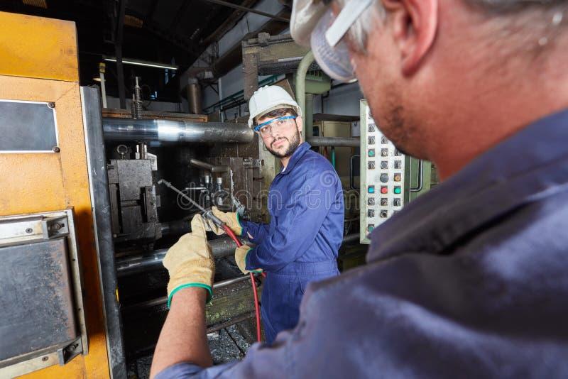 Trabajadores de la fundición que fabrican los objetos del metal foto de archivo