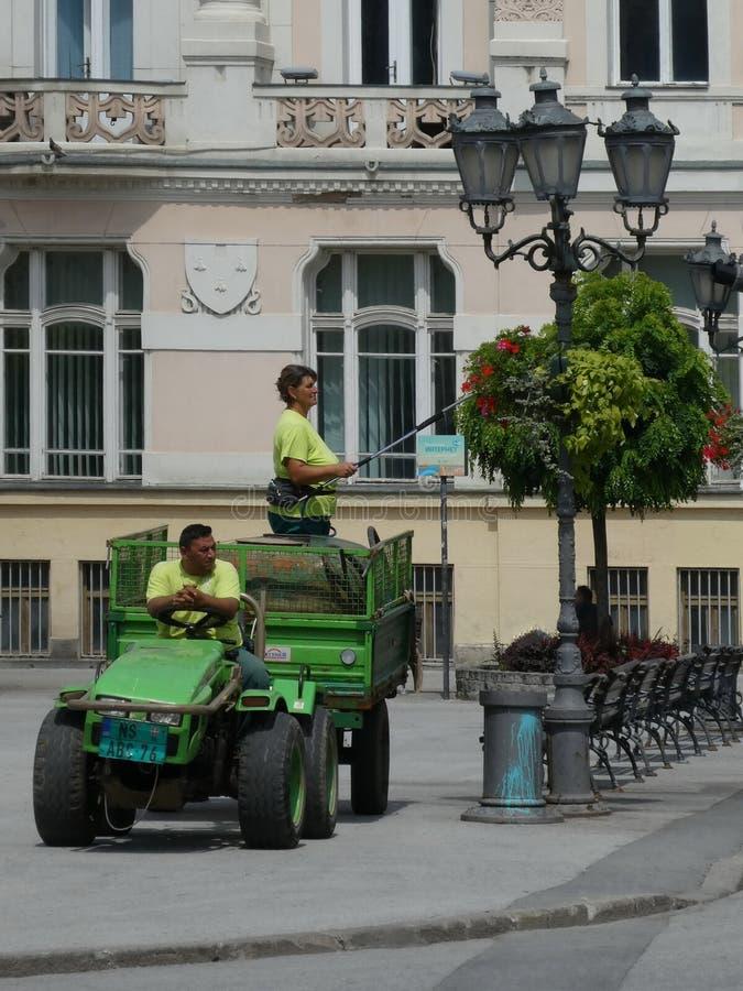 Trabajadores de las flores de riego del servicio del verdor de la ciudad en la lámpara de calle en día caliente taking foto de archivo libre de regalías