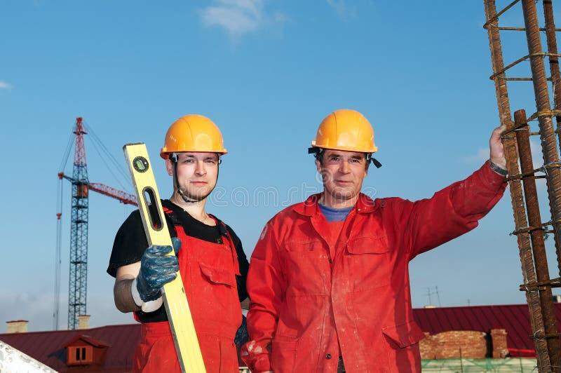 Trabajadores de los constructores en la construcción imagenes de archivo
