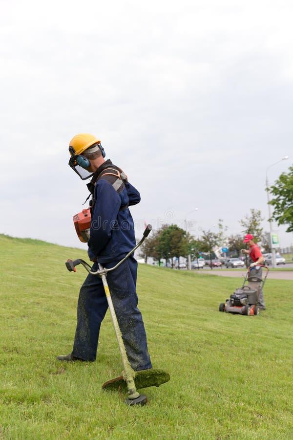 Trabajadores de los paisajistas que encienden el condensador de ajuste y el cortacésped del gas foto de archivo libre de regalías
