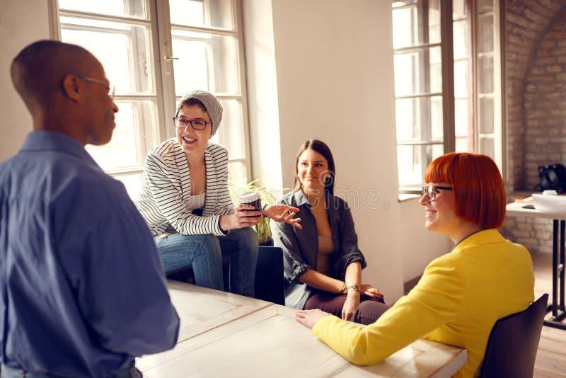 Trabajadores de sexo femenino en oficina que hablan con el encargado de sexo masculino imagenes de archivo