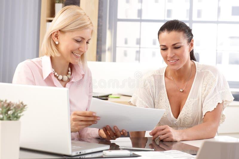 Trabajadores de sexo femenino felices en la oficina de negocios fotos de archivo libres de regalías