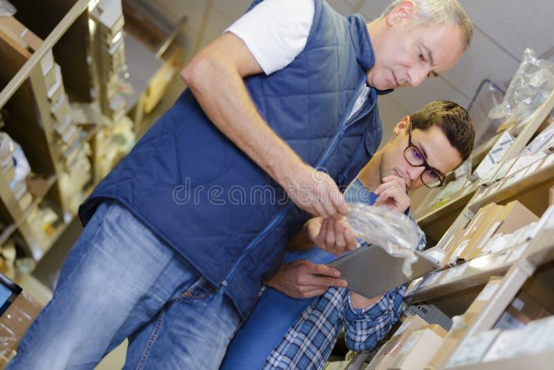 Trabajadores de sexo masculino en almacén imagenes de archivo