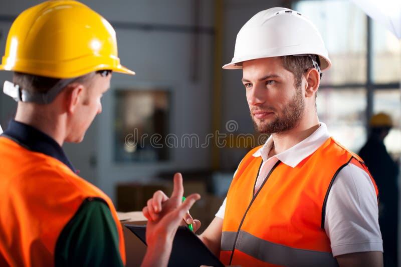 Trabajadores de Warehouse que consultan imagen de archivo