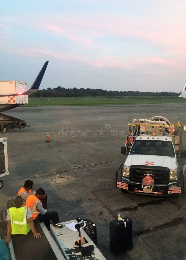 Trabajadores del aeropuerto que esperan equipaje cerca del avión imagenes de archivo