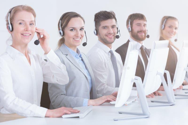 Trabajadores del centro de atención telefónica en oficina imagen de archivo libre de regalías