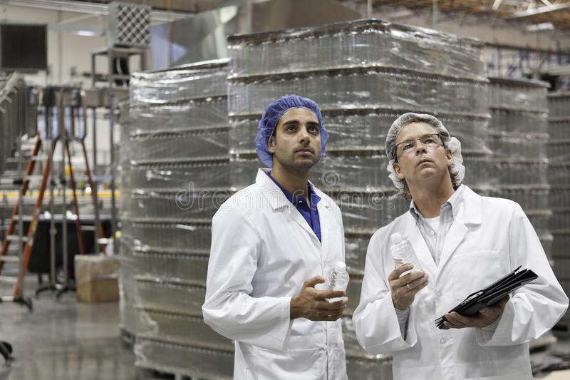 Trabajadores del control de calidad que examinan en la planta de embotellamiento fotografía de archivo