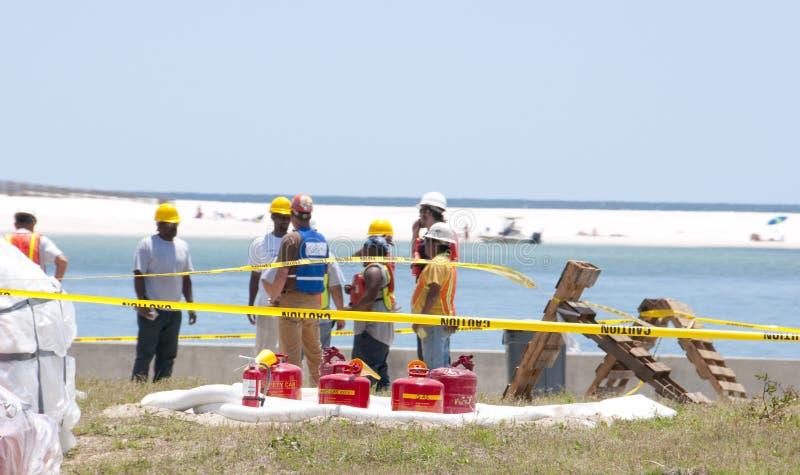 Trabajadores del derramamiento de petróleo en la costa imágenes de archivo libres de regalías
