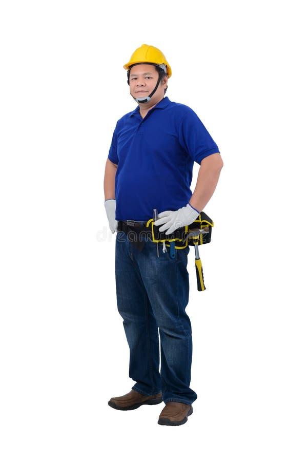 Trabajadores del hombre de la construcción en la camisa azul con los guantes protectores, casco con la correa de la herramienta a fotografía de archivo libre de regalías