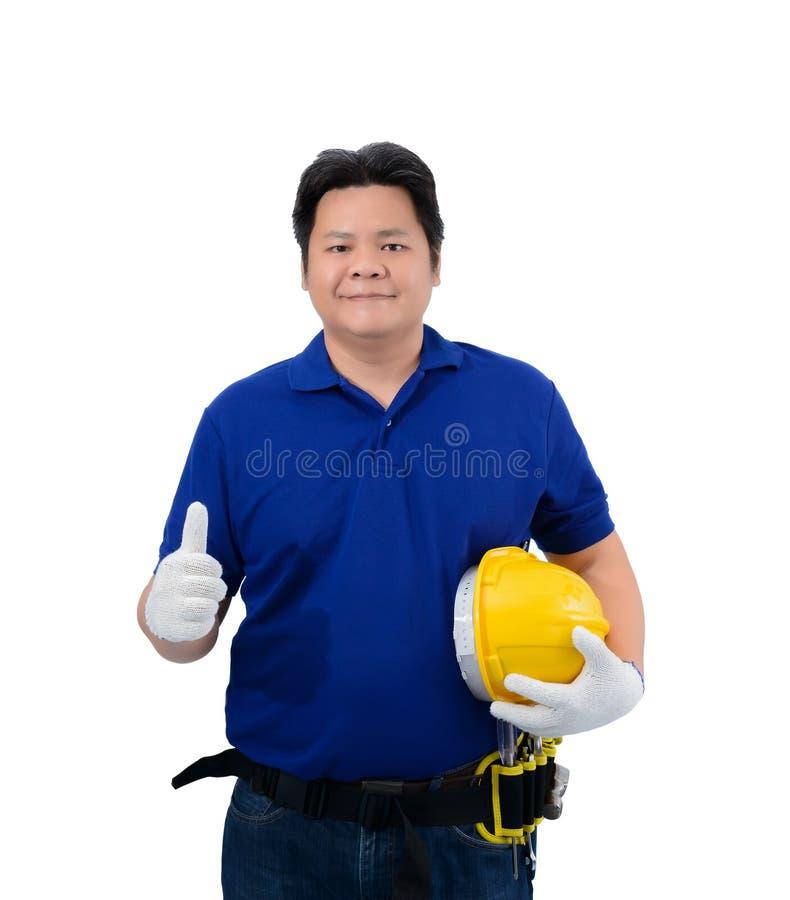 Trabajadores del hombre de la construcción en camisa azul con los guantes protectores, casco con la correa de la herramienta y lo imagen de archivo libre de regalías