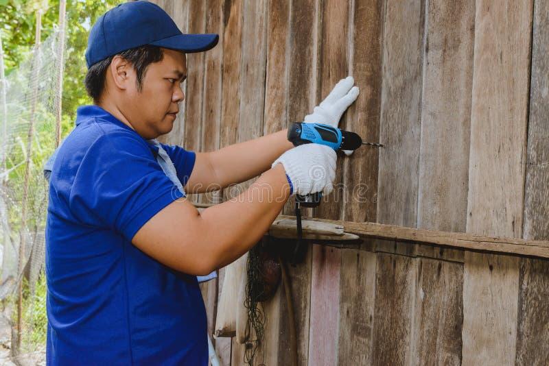Trabajadores del hombre de la construcción en camisa azul con los guantes protectores y el trabajo con el taladro de poder imagen de archivo libre de regalías
