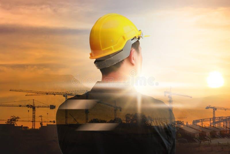 Trabajadores del ingeniero en el fondo de las grúas de construcción en fondo imágenes de archivo libres de regalías