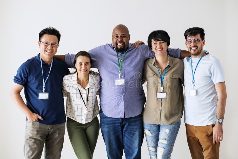 Trabajadores diversos que se colocan junto sonrientes imagen de archivo libre de regalías