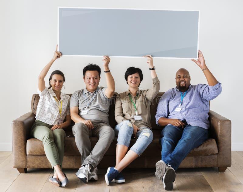 Trabajadores diversos que se sientan en el sofá que sostiene la bandera vacía fotografía de archivo