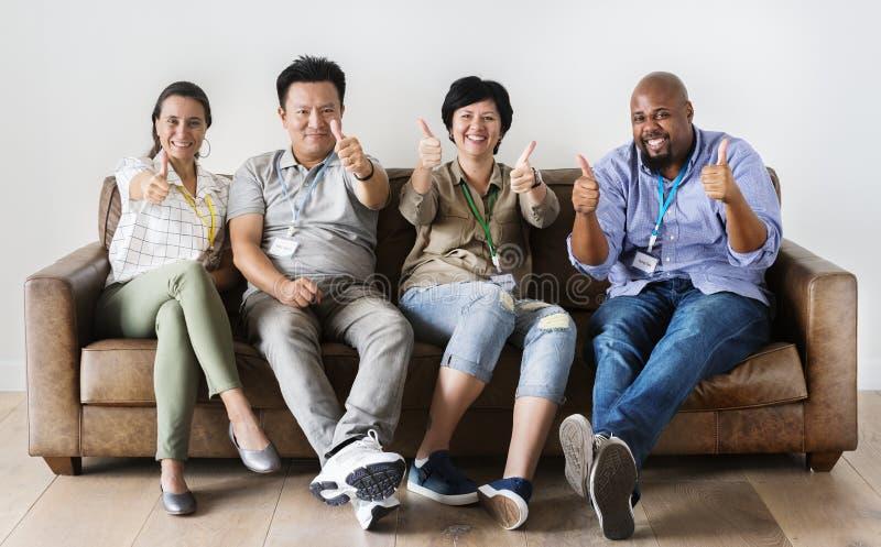 Trabajadores diversos que se sientan junto y que muestran el pulgar para arriba sobre el sofá foto de archivo libre de regalías