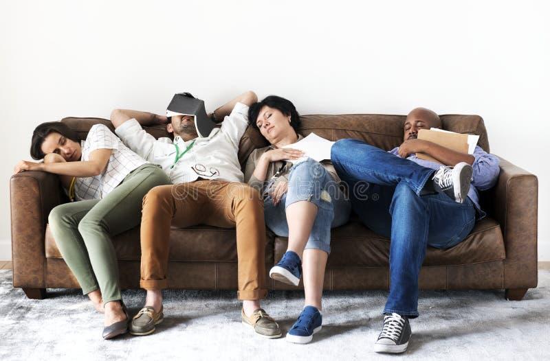 Trabajadores diversos que toman resto en el sofá imagenes de archivo