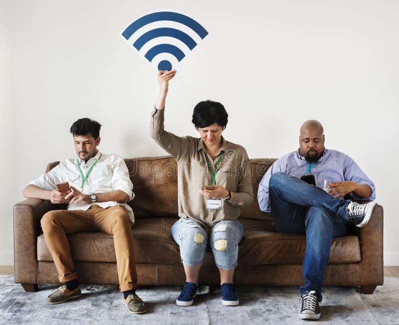Trabajadores diversos que trabajan en el teléfono móvil que se sienta en el sofá fotografía de archivo libre de regalías