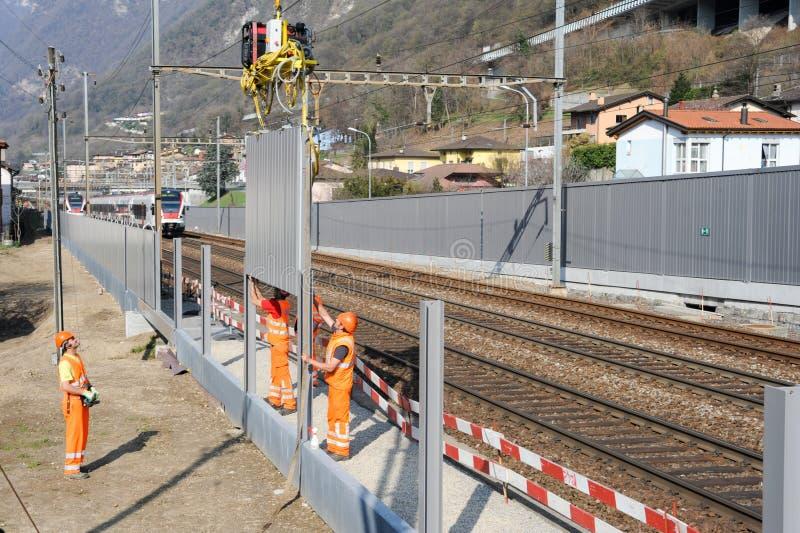 Trabajadores durante la instalación de barreras del ruido en el ferrocarril fotografía de archivo