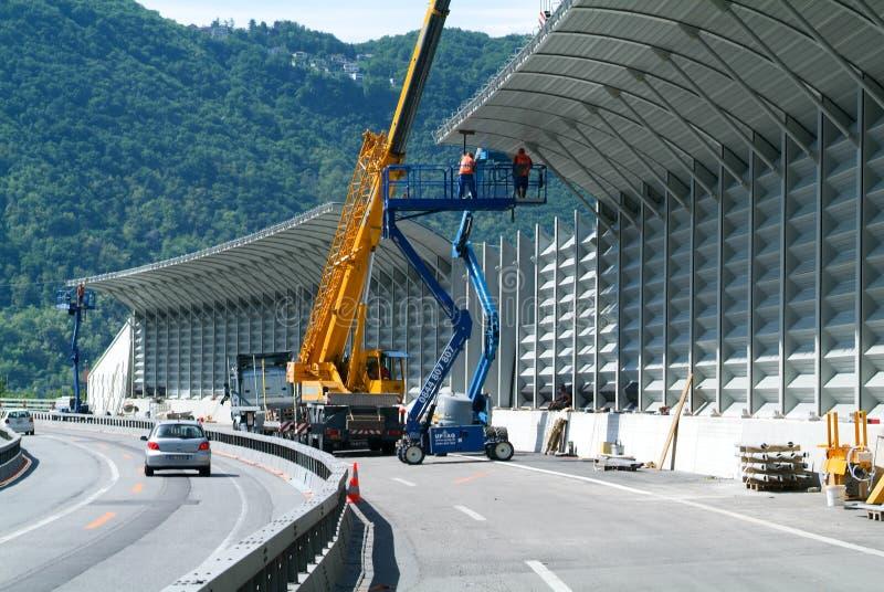 Trabajadores durante la instalación de barreras del ruido en la carretera fotos de archivo