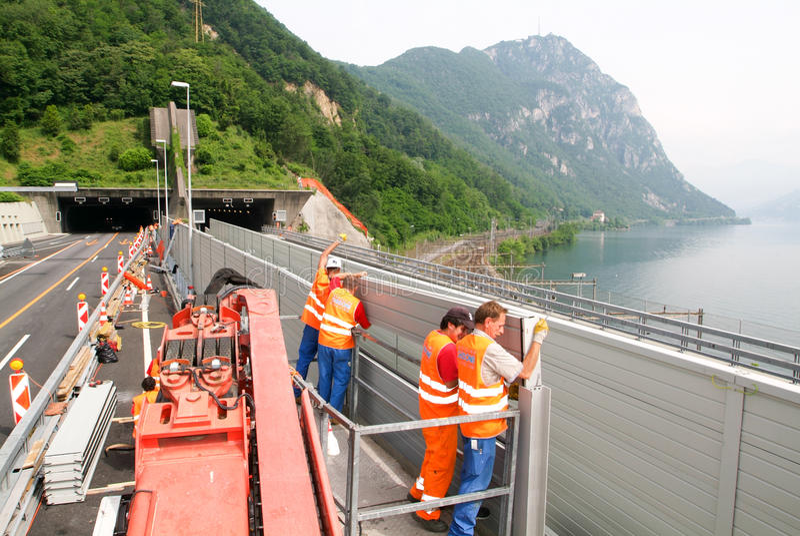 Trabajadores durante la instalación de barreras del ruido en la carretera foto de archivo