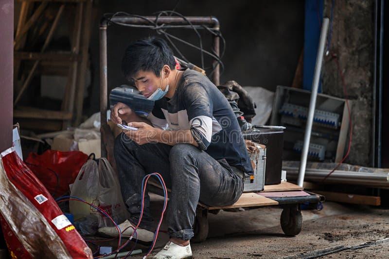 Trabajadores emigrantes que miran los teléfonos móviles mientras que descansa fotografía de archivo libre de regalías