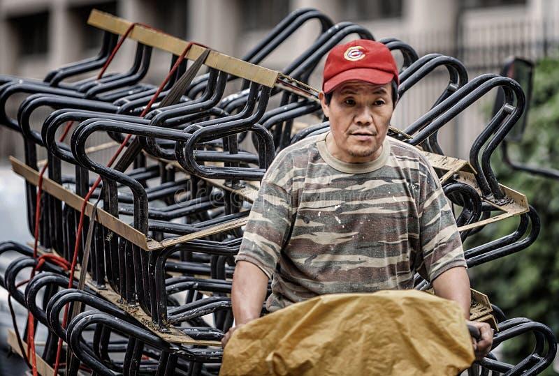 Trabajadores emigrantes que montan un triciclo imagen de archivo