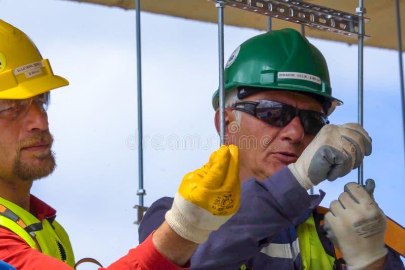 Trabajadores en cascos en el emplazamiento de la obra Construcciones foto de archivo
