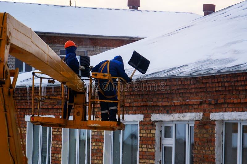 Trabajadores en guardapolvos y cascos anaranjados en la cesta de la gr?a quitar los car?mbanos del tejado de la casa en un d?a de foto de archivo