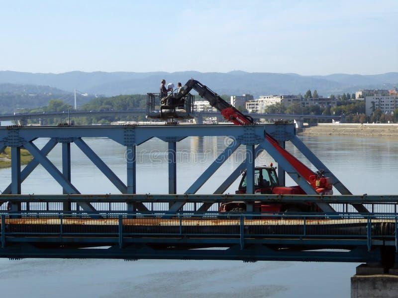 Trabajadores en la grúa con el funcionamiento aéreo hidráulico de la plataforma en el desmontaje del hierro fotografía de archivo