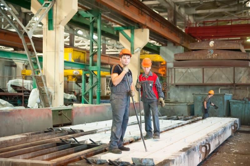 Trabajadores en la planta de los productos del ferrohormigón fotos de archivo libres de regalías