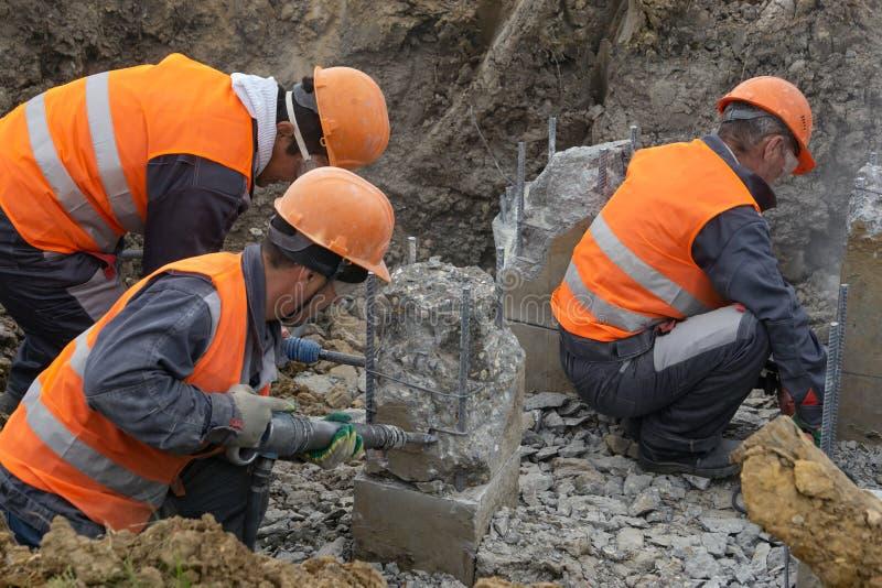 Trabajadores en la tajada del emplazamiento de la obra que se corta un martillo perforador llena fotografía de archivo libre de regalías