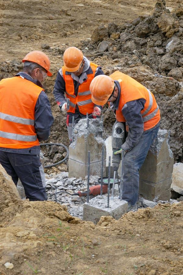 Trabajadores en la tajada del emplazamiento de la obra que se corta un martillo perforador llena foto de archivo libre de regalías