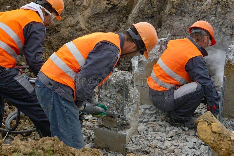 Trabajadores en la tajada del emplazamiento de la obra que se corta un martillo perforador llena fotos de archivo
